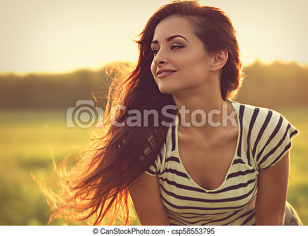 Beautiful smiling young woman looking happy with long amazing hair on nature bright sunset summer background. Closeup toned relaxing portrait - csp58553795