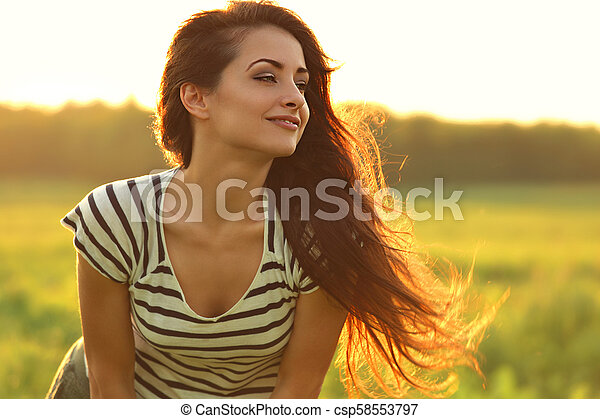 Beautiful smiling young woman looking happy with long amazing hair on nature bright sunset summer background. Closeup portrait - csp58553797