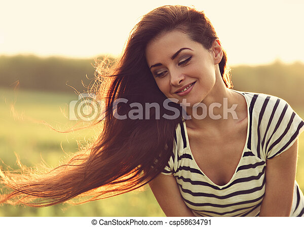 Beautiful smiling young woman looking happy with long amazing bright hair on nature bright sunset summer background. Closeup toned portrait - csp58634791