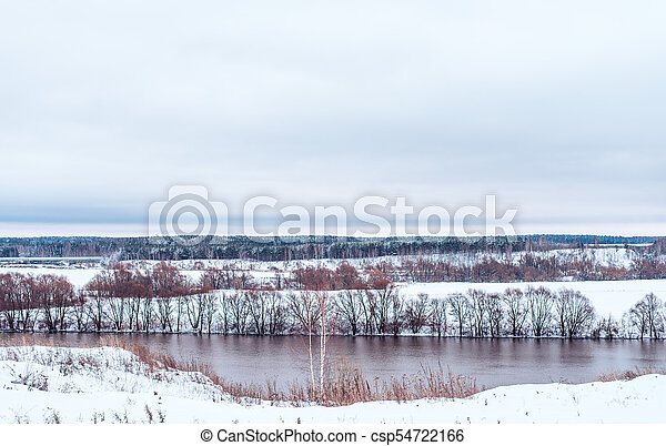 Beautiful snowy forest, on the background of the river in winter, snow-capped hills. - csp54722166