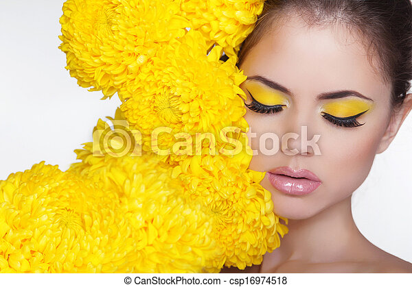 Beautiful Spa Woman over chrysanthemum flowers. Eyes makeup. Beauty Portrait. Perfect Fresh Skin. Pure Beauty Model Girl. Beautiful Face.  - csp16974518