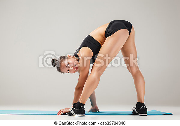 beautiful sporty girl standing in acrobat pose or yoga