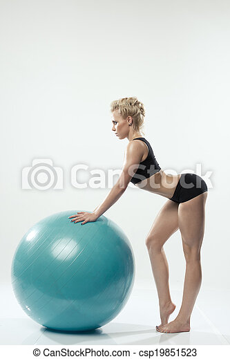Beautiful sporty woman doing stretching exercise with ball - csp19851523