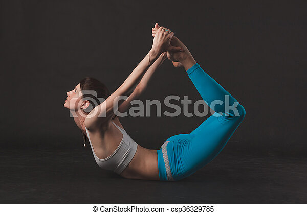 beautiful sporty yogi girl practices yoga asana over black
