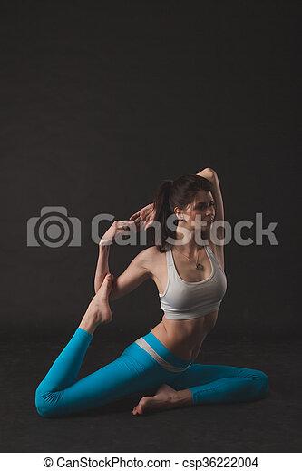 beautiful sporty yogi girl practices yoga asana over black