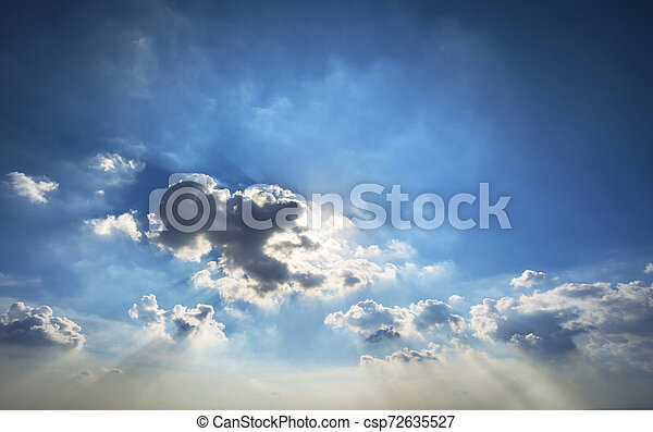 beautiful sun light through dramatic cloud against blue sky - csp72635527