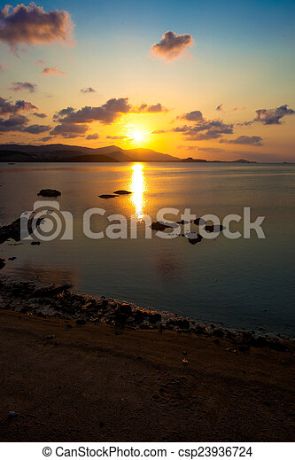 Beautiful sunset at the sea with mountains silhouettes - csp23936724