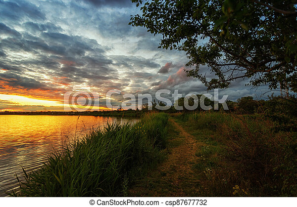 Beautiful sunset on the river, with soft effect, immediately after sunset, with a path along the shore, a tree in the foreground and trees in the distance - csp87677732
