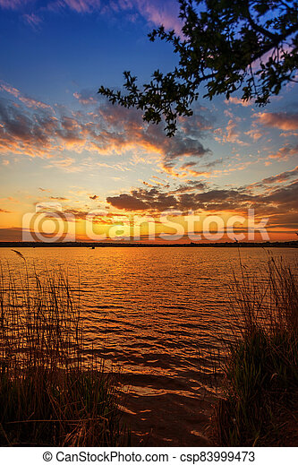 Beautiful sunset on the river with tree branches in the foreground - csp83999473