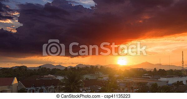 Beautiful sunset over a dark cityscape. - csp41135223