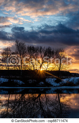 Beautiful sunset over the landscape with a river in March - csp88711474