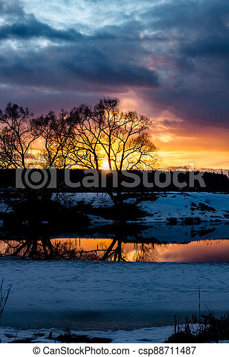 Beautiful sunset over the landscape with a river in March - csp88711487