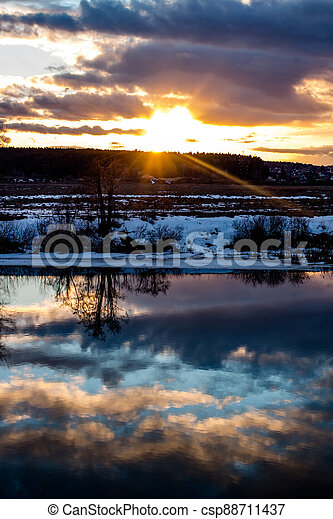 Beautiful sunset over the landscape with a river in March - csp88711437