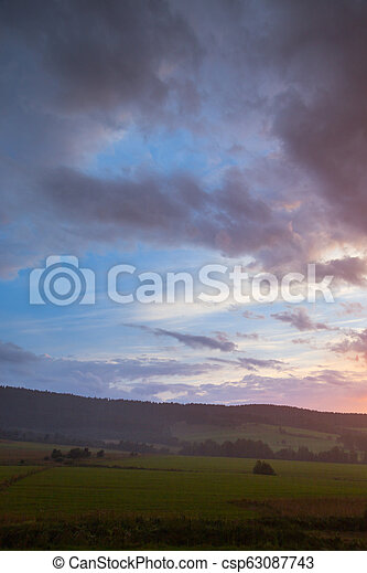 Beautiful sunset sky. Landscape with cloudy sky, trees, meadow and hill - csp63087743
