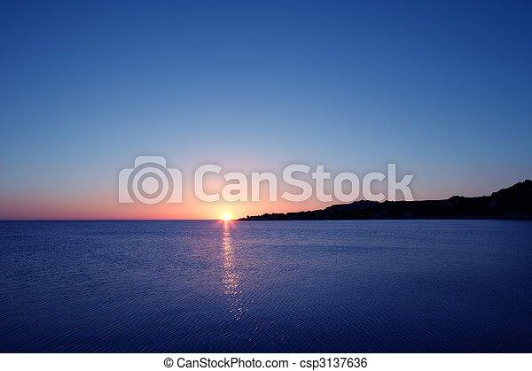Beautiful sunset sunrise over blue sea ocean red  sky - csp3137636