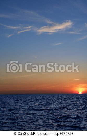 Beautiful sunset sunrise over blue sea ocean red  sky - csp3670723