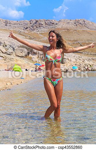Beautiful Tanned Girl In A Bikini Standing In A Water Csp43552860