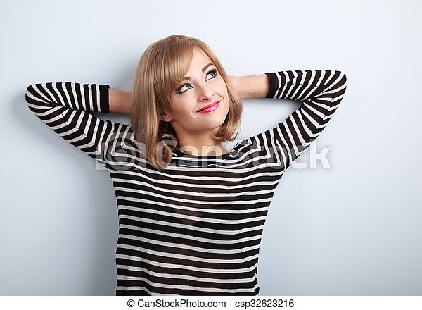 Beautiful thinking blond young woman in sweater looking up on blue background - csp32623216