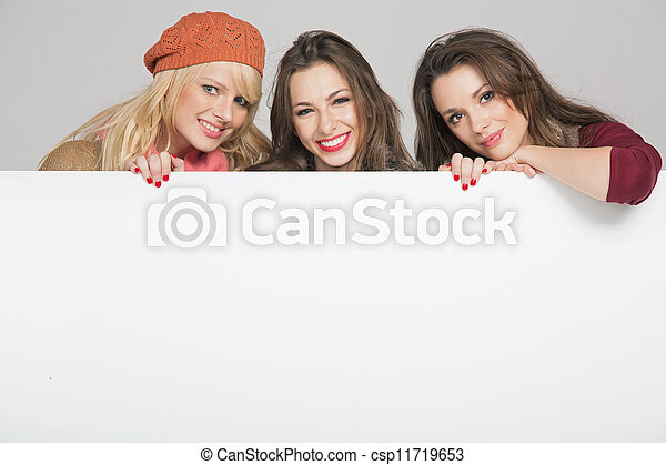 Beautiful three female friends with empty board - csp11719653