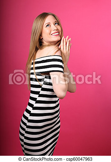 Beautiful toothy smiling blond long stright hairstyle woman in love dreaming and looking up waiting the gift on pink background - csp60047963