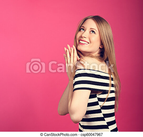 Beautiful toothy smiling blond long stright hairstyle woman in love dreaming and looking up waiting the gift on pink background - csp60047967
