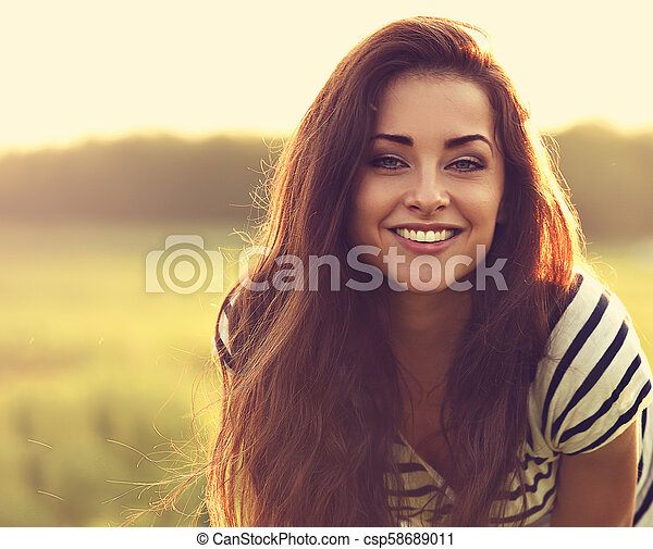 Beautiful toothy smiling young woman looking happy with long amazing bright hair on nature bright sunset summer background. Closeup toned color portrait - csp58689011