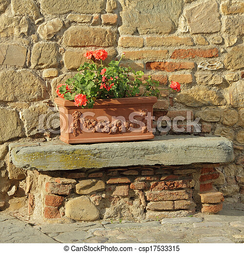 beautiful tuscan terracotta planter in front of  old stone and brick house, Italy, Europe - csp17533315