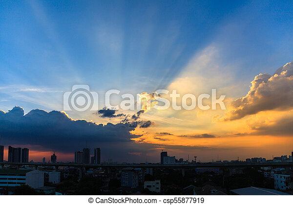 Beautiful twilight sky at sunset over a dark cityscape - csp55877919