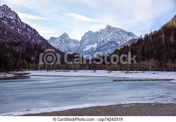 Beautiful view at sunset of the peaceful lake Fucine Tarvisio, Italy with green forest and snowy mountains in the background . - csp74243319