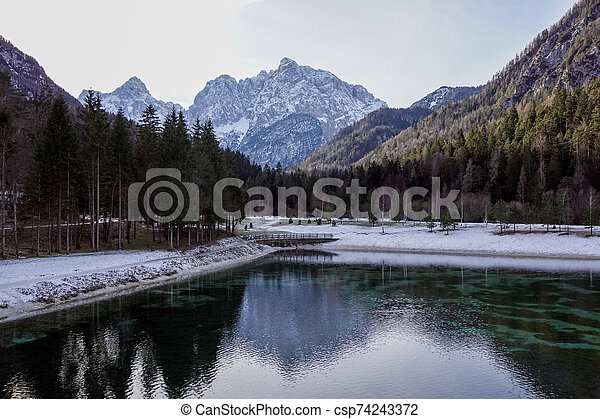 Beautiful view at sunset of the peaceful lake Fucine Tarvisio, Italy with green forest and snowy mountains in the background . - csp74243372