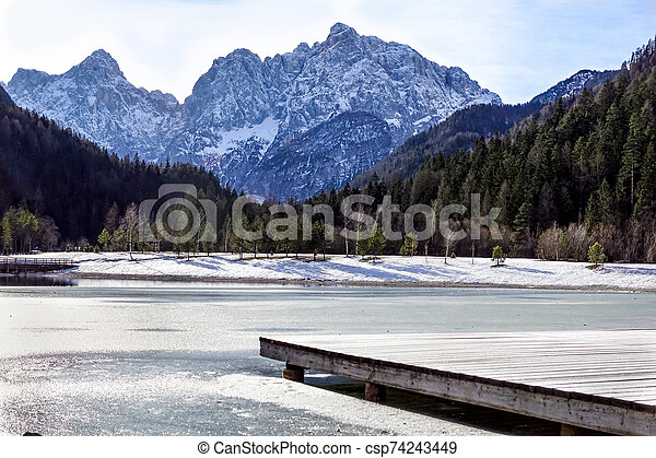 Beautiful view at sunset of the peaceful lake Fucine Tarvisio, Italy with green forest and snowy mountains in the background . - csp74243449