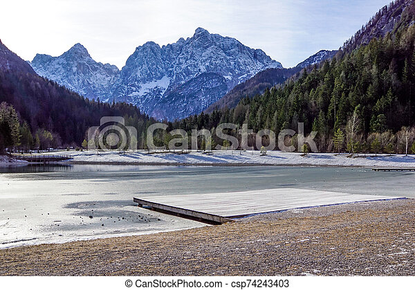 Beautiful view at sunset of the peaceful lake Fucine Tarvisio, Italy with green forest and snowy mountains in the background . - csp74243403