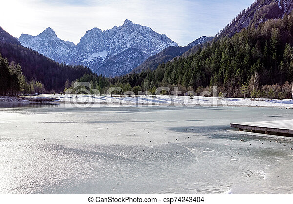 Beautiful view at sunset of the peaceful lake Fucine Tarvisio, Italy with green forest and snowy mountains in the background . - csp74243404