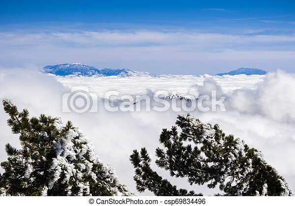 Beautiful view from high above the clouds towards the summit of Mt San Gorgonio and Mt San Jacinto, visible in the background; photo taken from Mount San Antonio (Mt Baldy), Los Angeles county - csp69834496