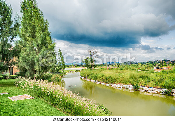 Beautiful view of a small lake edged by green trees at autumn cloudy evening. - csp42110011