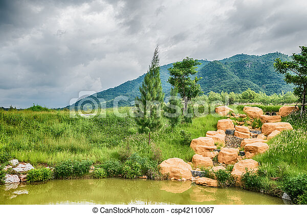 Beautiful view of a small lake edged by green trees at autumn cloudy evening. - csp42110067