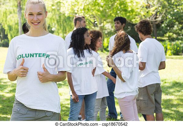 Beautiful volunteer gesturing thumbs up  - csp18670542