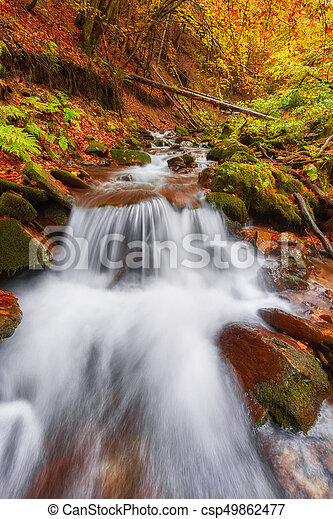 Beautiful waterfall at mountain river in colorful autumn forest with red and orange leaves at sunset. - csp49862477