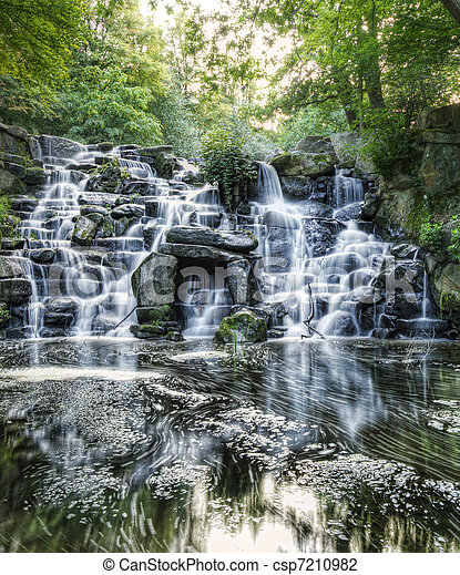 Beautiful waterfall cascades over rocks in lush forest landscape - csp7210982