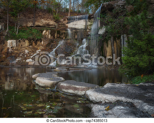 Beautiful waterfall in the rays of the evening sun. Waterfall in autumn - csp74385013
