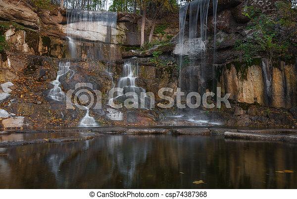 Beautiful waterfall in the rays of the evening sun. Waterfall in autumn - csp74387368