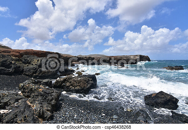 Beautiful Waves Crashing on Black Sand Stone Beach in Aruba - csp46438268
