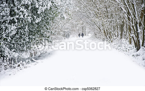 Beautiful winter forest snow scene with deep virgin snow and family walking dogs on path walkway - csp5062827