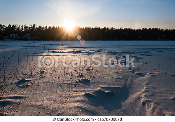 Beautiful winter scene. Sunset at the frozen lake covered with snow. - csp78700078