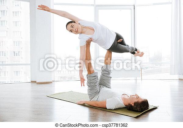 beautiful woman balancing doing acro yoga with partner in