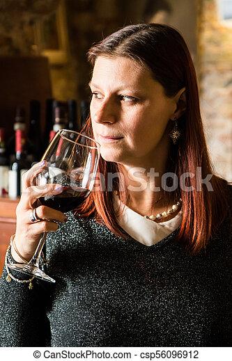 beautiful woman drinking glass of wina in a wine cellar - csp56096912
