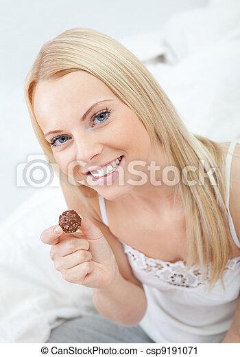 Beautiful woman eating chocolate - csp9191071