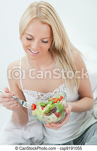 Beautiful woman eating green salad - csp9191055
