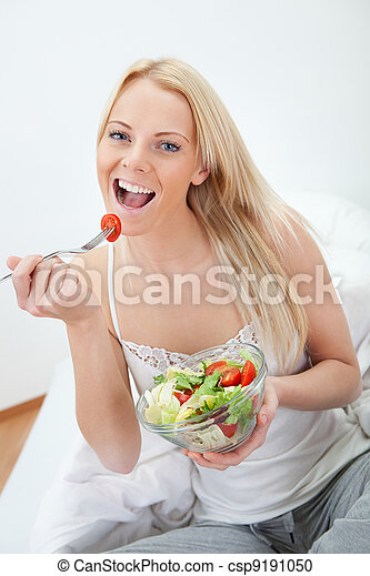 Beautiful woman eating green salad - csp9191050