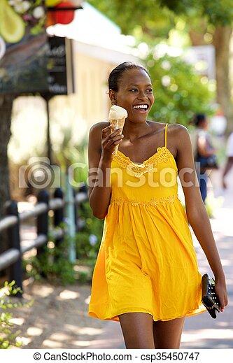 Beautiful woman eating ice cream on street - csp35450747